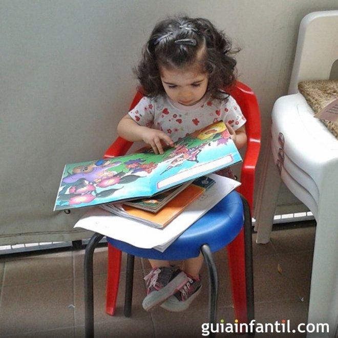 Micaela, de 1 año, con un cuento con imágenes