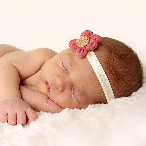 Una bebé durmiendo con su diadema