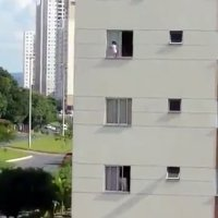 Un bebé juega en la repisa de una ventana de un tercer piso