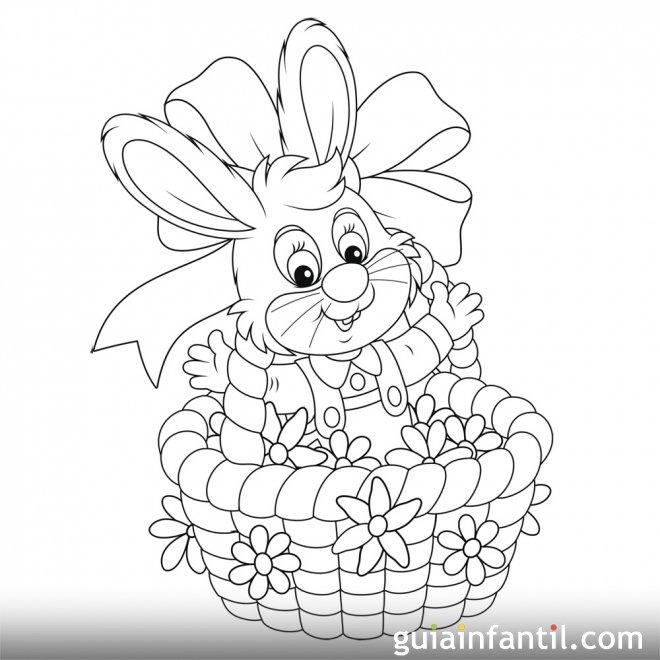 Conejo dentro de una cesta llena de huevos de Pascua