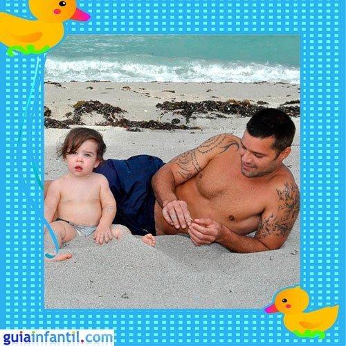 El cantante puertorriqueño con uno de sus hijos gemelos en la playa