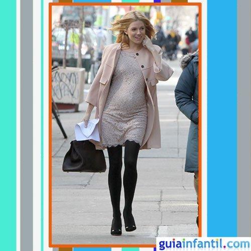 La actriz Sienna Miller embarazada con vestido y abrigo rosa palo