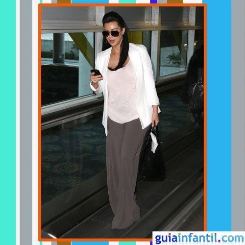 La celebrity Kim Kardashian embarazada con pantalón ancho y americana