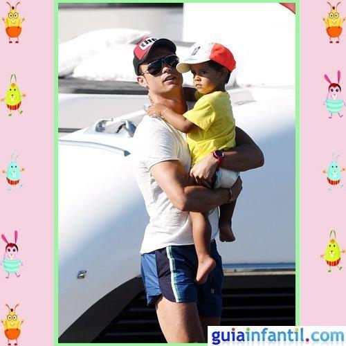 El futbolista Cristiano Ronaldo y su hijo con bañador, camiseta y gorra