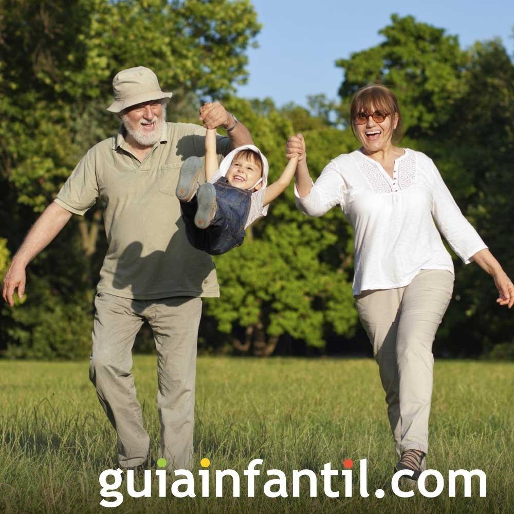 Abuelos que juegan a columpiar a los nietos