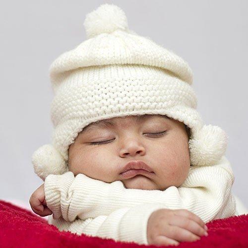 Foto de bebé bien abrigado durmiendo