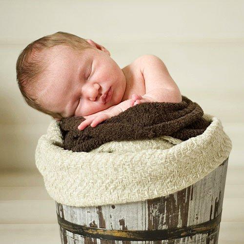 Bebé durmiendo en el cesto de la ropa
