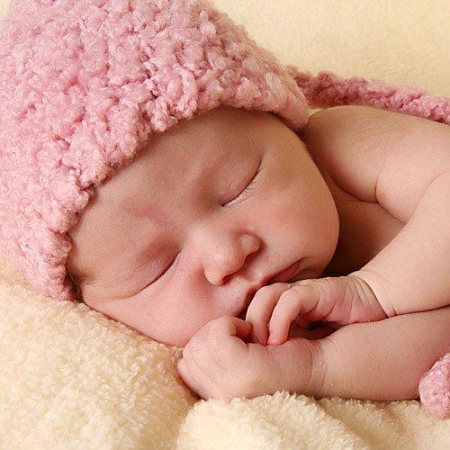 Foto de bebé dormido con albornoz rosa