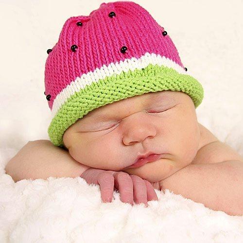 Un bebé durmiendo con su gorrito de sandía