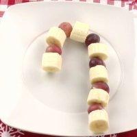 Postre de fruta navideño. Bastón de caramelo para niños