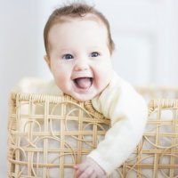 Bebé riéndose al romper un papel