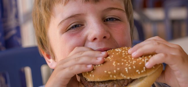 Niño come hamburguesa