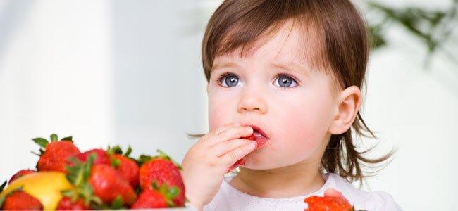 Niña come fresas