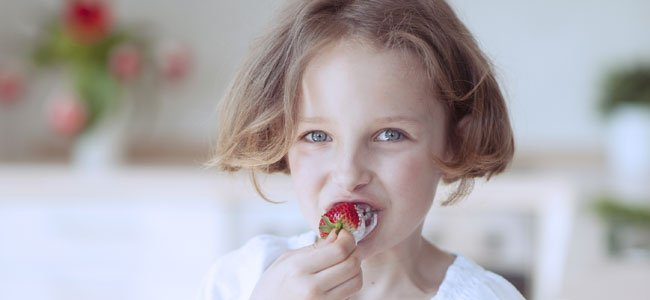 Niña come fresa