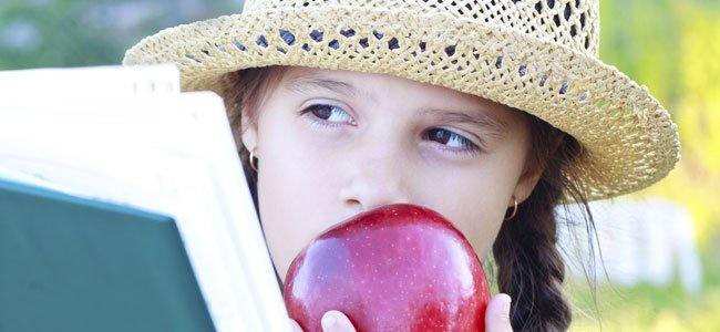 NIña come manzana mientras lee