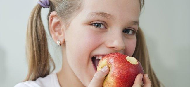 Niña muerde manzana