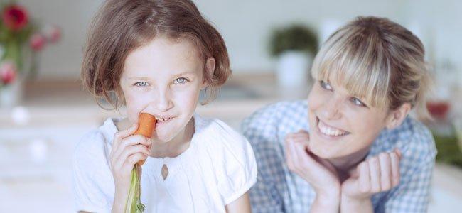 Niña come zanahoria