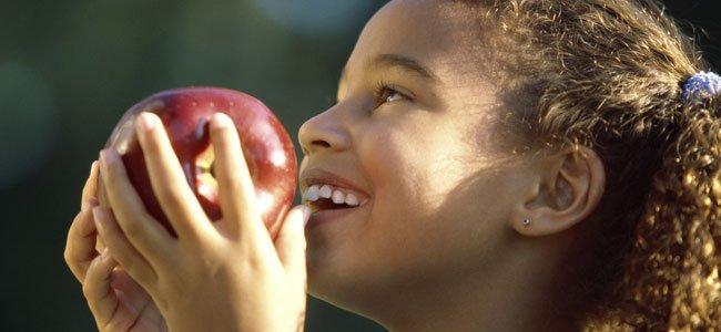 Niña come manzana