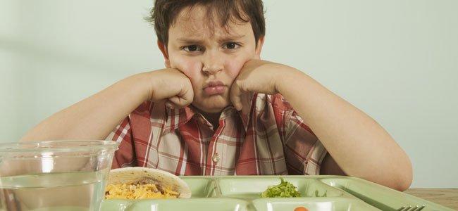 NIño triste con bandeja comida