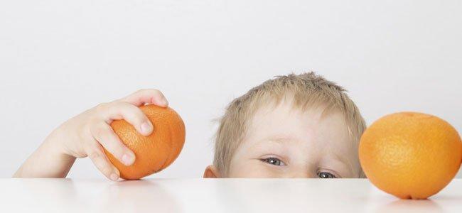 Niño agarra naranja