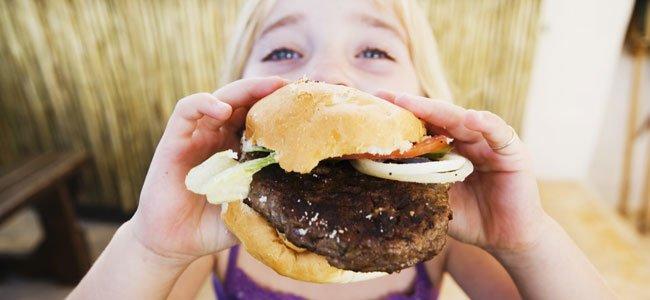 Niño come hamburguesa