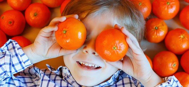 Niño con mandarina