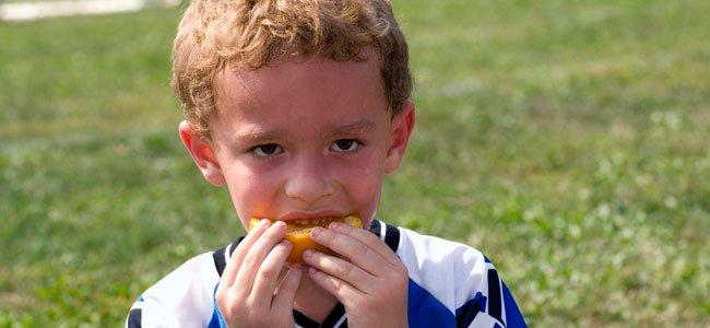 Niño come naranja