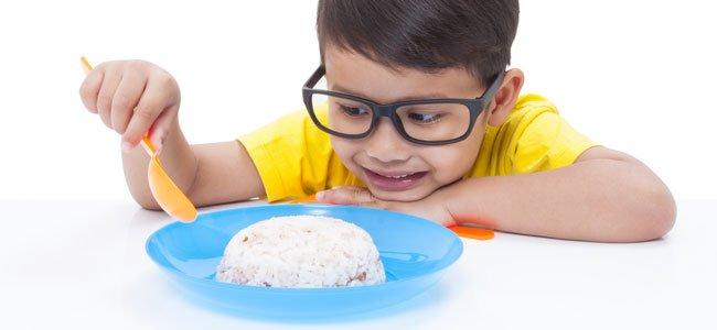 Niño come arroz