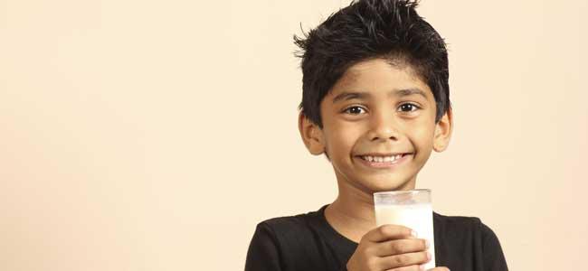 Niño bebe leche en vaso