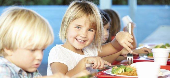 Niños comen en comedor