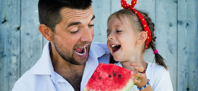 Padre con niña come sandía