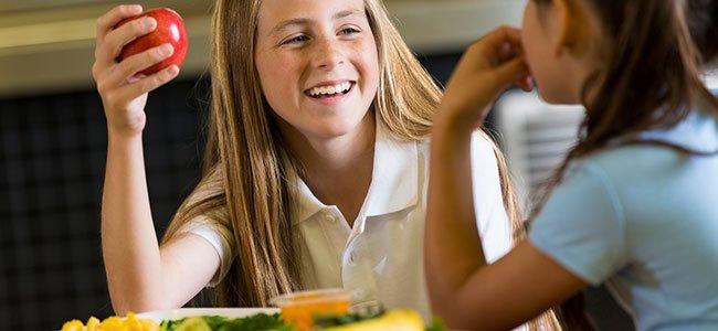 Niño adolescente come manzana