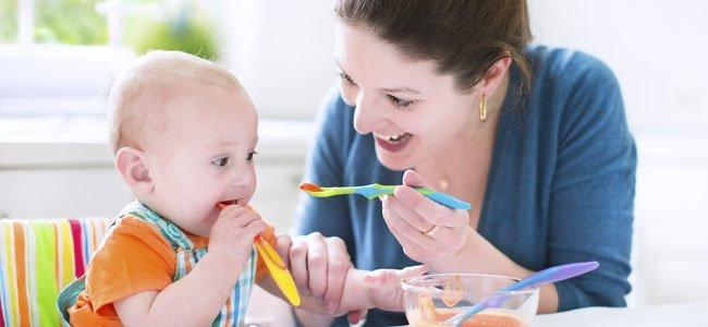 Madre da de comer a bebé