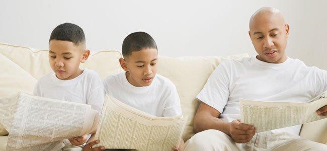 Padre lee con hijos periódico