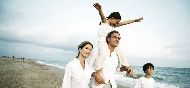 Padres con hijos pasean por playa