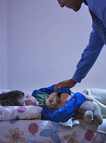 Padre despierta el hijo en la cama