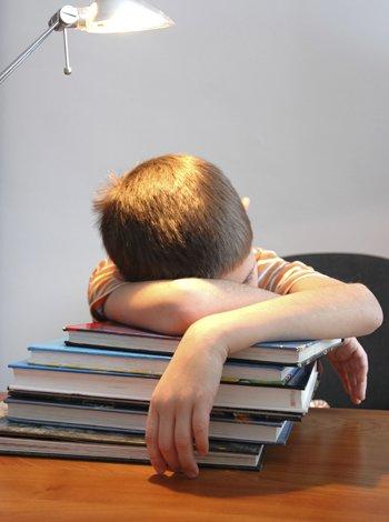Niño durmiendo encima de los libros