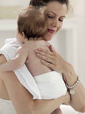 Bebé eructa en brazos de su madre