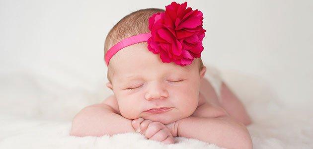 bebé con flor rosa en la cabeza