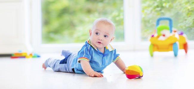 Bebé con pelota en el suelo
