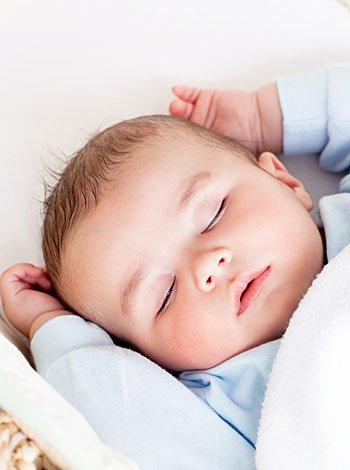 Bebé duerme boca arriba en la cuna