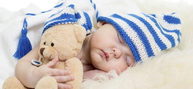 Bebé duerme abrazado a un osito de peluche