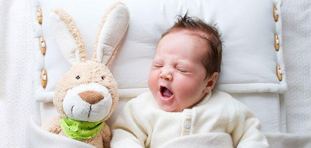 bebé bostezando en cuna con muñeco
