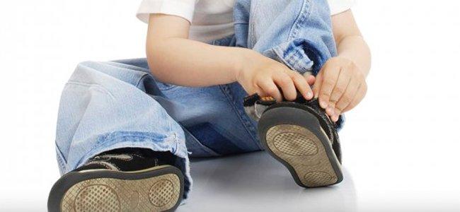 Niño amarra cordón zapatillas, niño autónomo