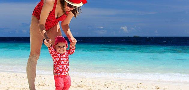 Niño aprende a andar en la playa