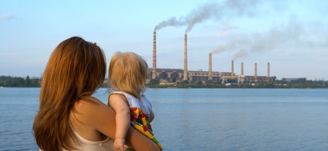 Madre con bebé miran fábricas