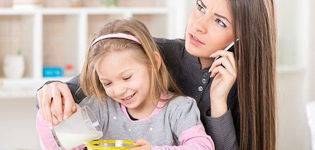 Madre sirve a su hija mientras habla por el movil
