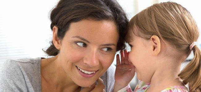NIña dice algo a su madre al oido