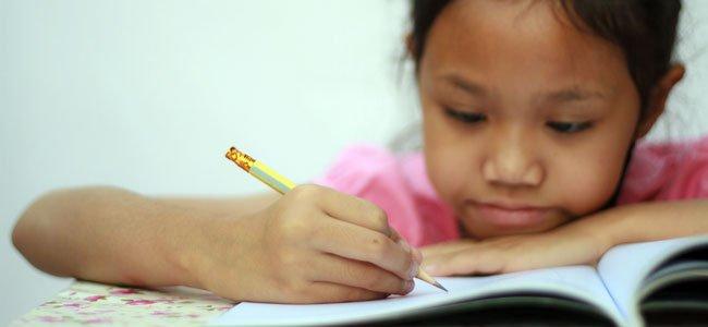 Niña escribe a mano