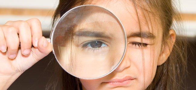 Niña con lupa en el ojo